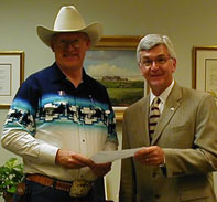 Cowboy Poet Lariat Ron Wilson presents an original cowboy poem to Chuck Shroeder for inclusion at the National Cowboy Hall of Fame.